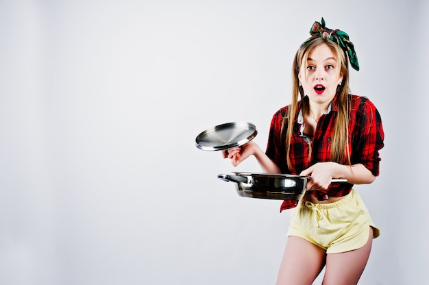 Young funny housewife in checkered shirt and yellow shorts pin up style with frying pan isolated