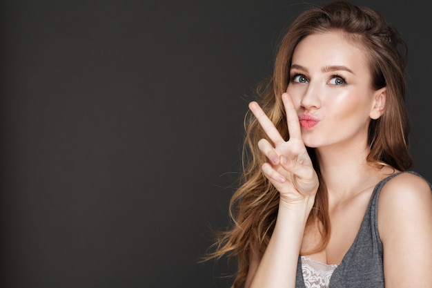 Young funny lady posing while make peace gesture.