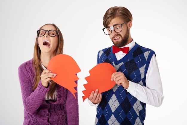 Giovani coppie di sguardo divertente del geek che si separano in su isolato