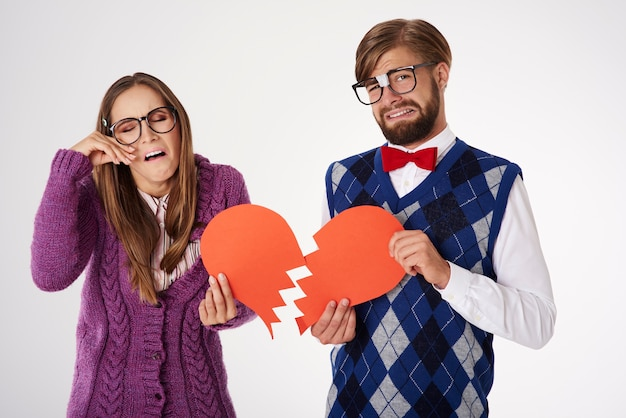 Young funny looking geek couple breaking up isolated