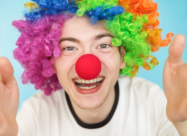 Young funny male teenager in white t-shirt on blue background in clown wig close-up portrairt