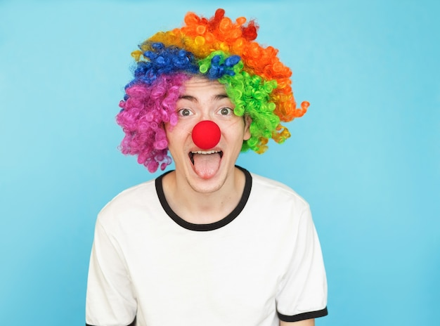 Young funny male teenager in white t-shirt on blue background in clown wig