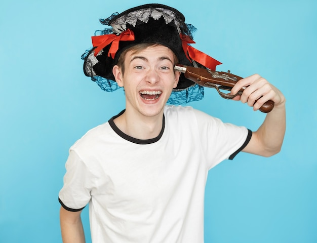 Young funny male teenager in white t-shirt on blue background in pirate hat and gun in hand wants to shoot in head