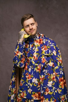 Young funny man in floral clothes using a banana as a telephone