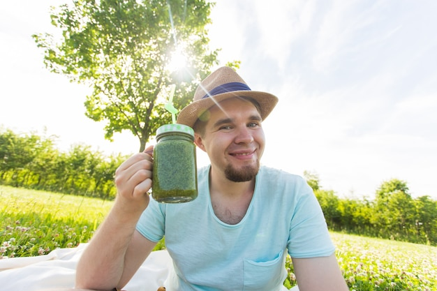 若いおかしな男は、ストローでデトックススムージーを保持しています。健康的なライフスタイル、人と食べ物の概念。