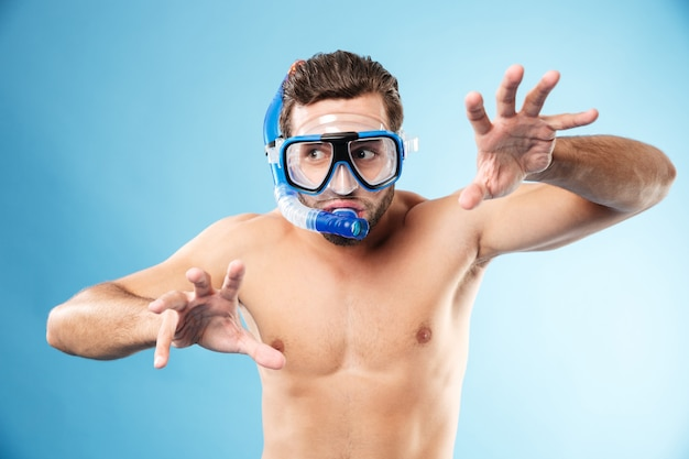 Young funny man playing with hands and wearing water mask