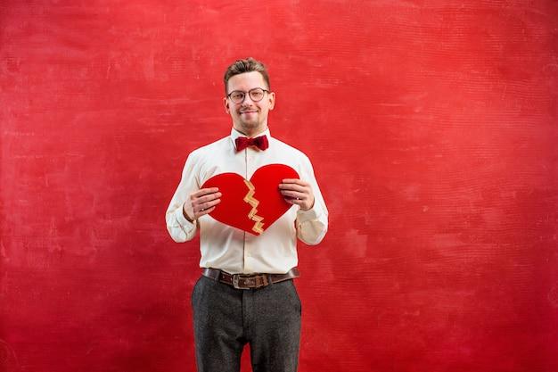 Giovane uomo divertente con cuore spezzato e incollato astratto su sfondo rosso studio.