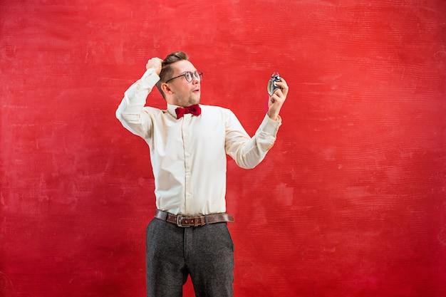 Giovane uomo divertente con orologio astratto su sfondo rosso studio.
