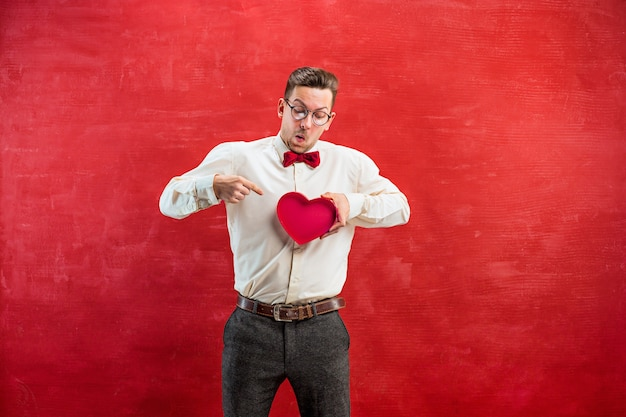 Young funny man with abstract heart and clock on red studio background.