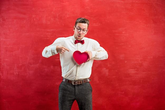 Giovane uomo divertente con cuore astratto e orologio su sfondo rosso studio.