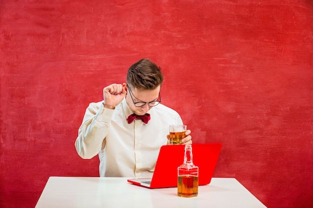 Young funny man with cognac sitting with laptop at st. valentine's day on red studio background.