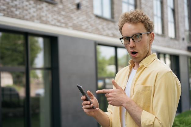 オンラインショッピングのためのモバイルアプリを使用して感情的な顔を開いた口を持つ若い面白い男