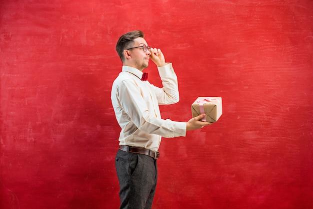 Giovane uomo divertente con regalo su sfondo rosso studio