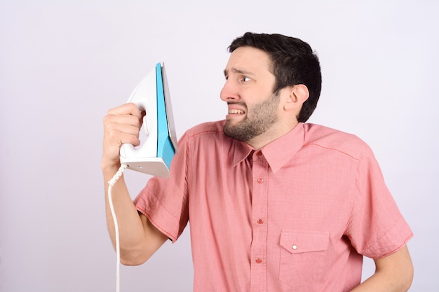Young funny man with an iron.