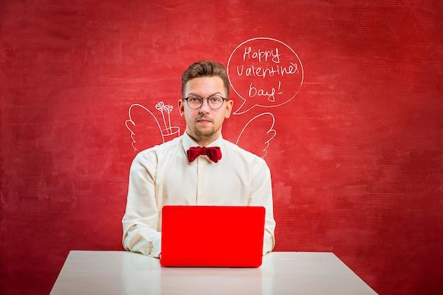 コピースペースと赤いスタジオの背景に聖バレンタインの日にラップトップを持つ若い面白い男