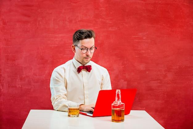 Giovane uomo divertente con il computer portatile a san valentino