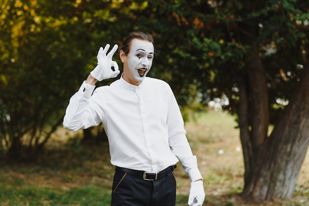 Young funny mime shows something.