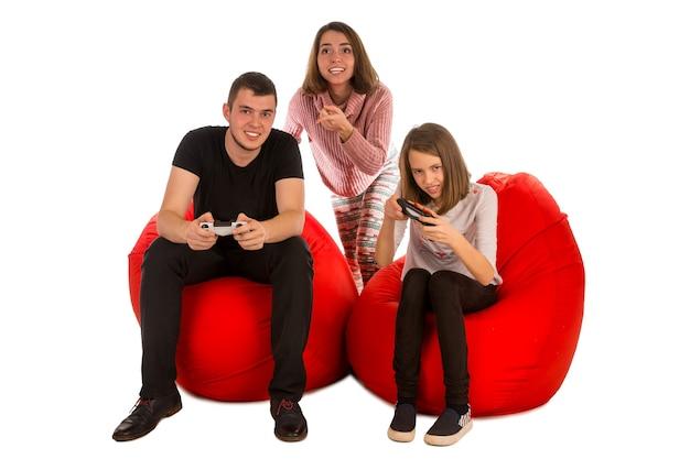 Молодые забавные люди с энтузиазмом играют в видеоигры, сидя на красных креслах-мешках, изолированных на белом