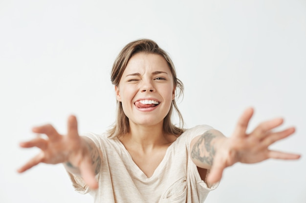 Young funny pretty girl winking showing tongue stretching hands to camera .