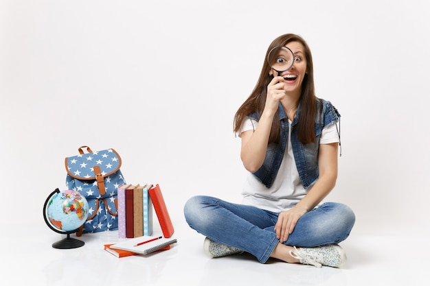Young funny pretty woman student holding and looking on magnifying glass sitting near globe, backpack, school books isolated
