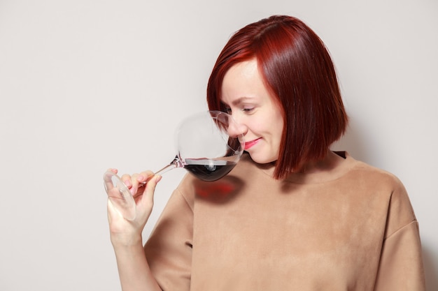 Young funny redhaired woman sommelier with wine glass