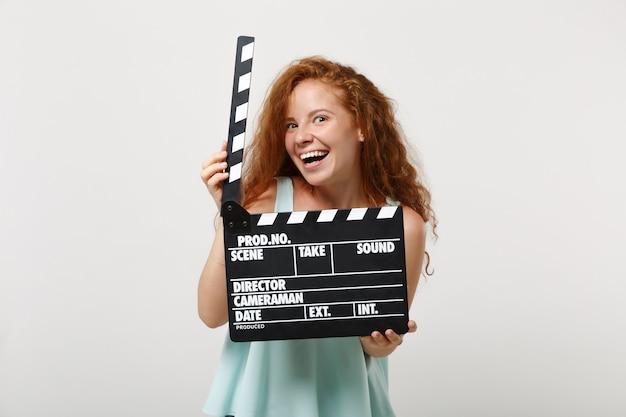 スタジオで白い壁の背景に分離されたポーズをとってカジュアルな明るい服を着た若い面白い赤毛の女性の女の子。人々のライフスタイルの概念。コピースペースをモックアップします。カチンコを作る古典的な黒いフィルムを保持しています。