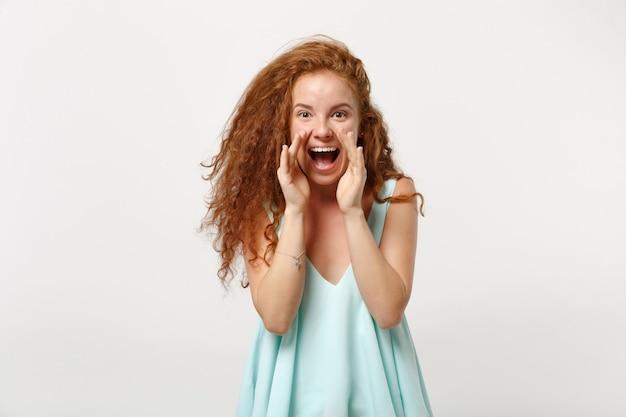 白い壁の背景、スタジオの肖像画に分離されたポーズでカジュアルな明るい服を着た若い面白い赤毛の女性の女の子。人々のライフスタイルの概念。コピースペースをモックアップします。口の近くで手のジェスチャーで叫ぶ。