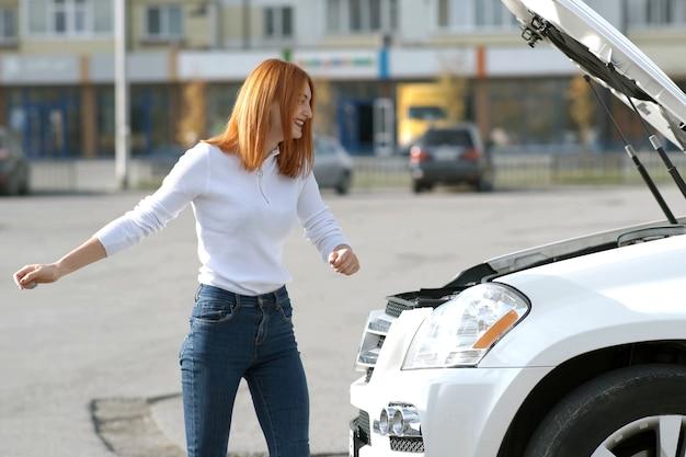 Молодая смешная улыбающаяся женщина-водитель возле разбитой машины с лопнувшим капотом, у которой возникла проблема с поломкой автомобиля, ожидая помощи