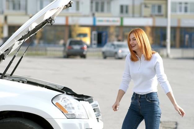 Молодая смешная улыбающаяся женщина-водитель возле разбитой машины с выскочившим капотом, у которой возникла проблема с поломкой автомобиля, ожидая помощи.