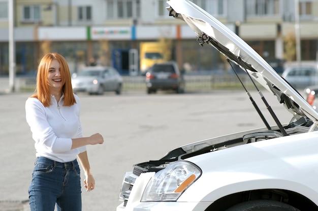 Молодая смешная улыбающаяся женщина-водитель возле разбитой машины с выскочившим капотом, у которой возникла проблема с поломкой, когда ее автомобиль ждет помощи.