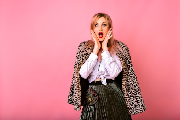Young funny surprised shocked woman posing on pink background , wearing white shirt and leopard coat, powerful emotions.