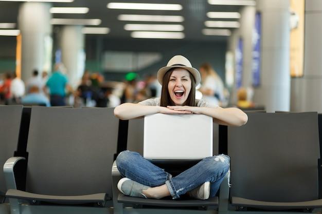 Giovane turista divertente viaggiatrice seduta con il computer portatile con le gambe incrociate mentre aspetta nella hall dell'aeroporto internazionale international
