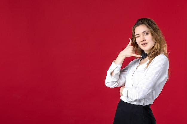 首に若い面白いウェイトレスの女性の蝶と赤い背景のジェスチャーを呼んで