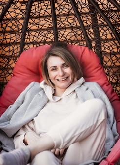 Молодая смешная женщина проводит время на открытом воздухе в плетеном стуле