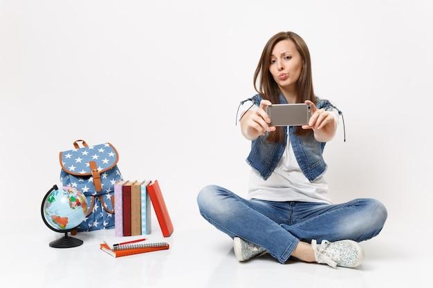 Giovane studentessa divertente che fa scattare selfie sul telefono cellulare e soffiare le labbra seduto vicino allo zaino del globo, libri di scuola isolati