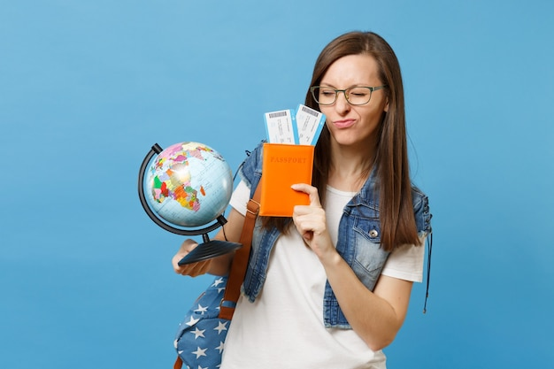 Young funny woman student in glasses with backpack holding world glove, passport, boarding pass tickets isolated on blue background. education in university college abroad. air travel flight concept.