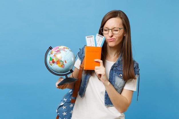 Молодой смешной студент-женщина в очках с рюкзаком, держащим перчатку мира, паспорт, билеты на посадочный талон, изолированные на синем фоне. обучение в вузе за рубежом. концепция полета авиаперелета.