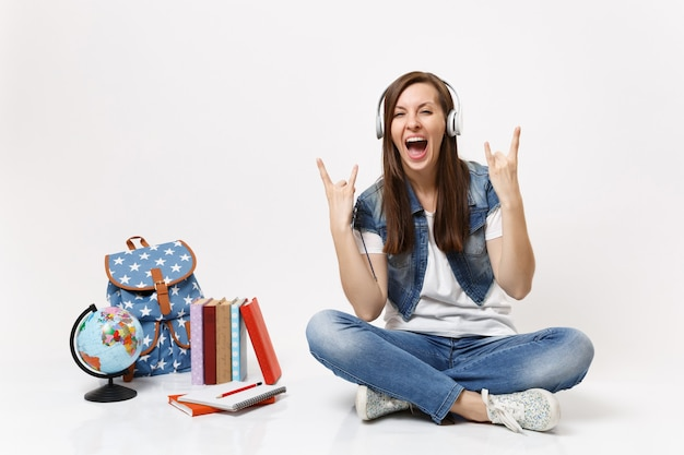 Young funny woman student with headphones listening music showing rock-n-roll sign screaming near globe backpack school books isolated on white wall