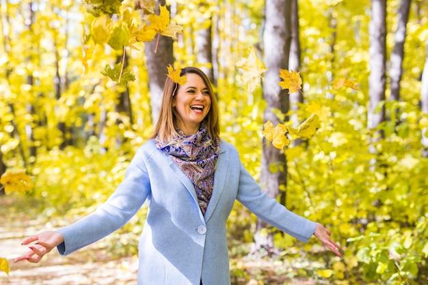 秋の公園で葉を投げる若い面白い女性