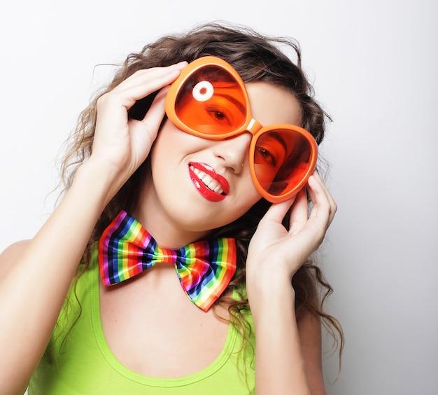 Молодая смешная женщина с большими оранжевыми солнцезащитными очками над белой
