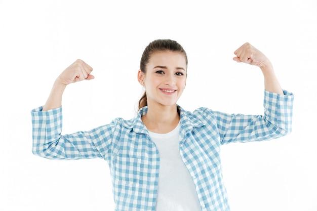 Молодая смешная молодая женщина показывая изолированные мышцы