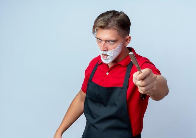 Молодой разъяренный светловолосый парикмахер в униформе измазал лицо пеной для бритья, держа опасную бритву на белом фоне с копией пространства