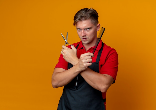 Young furious blonde male barber in uniform crosses hands holding scissors and comb