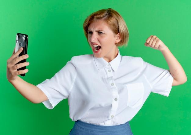 La giovane ragazza russa bionda furiosa esamina il telefono con il pugno alzato pronto a perforare isolato su fondo verde con lo spazio della copia