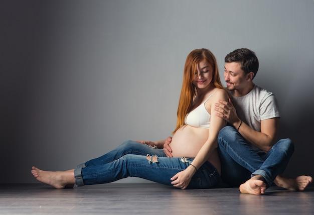 Молодые будущие родители мужчина и рыжая беременная женщина обнимаются на сером фоне