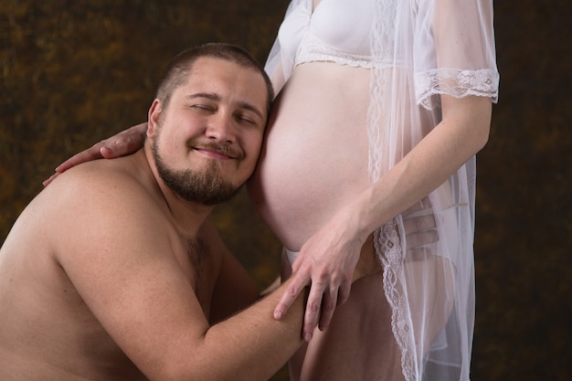 Молодые будущие родители мужчина и рыжая беременная женщина обнимаются