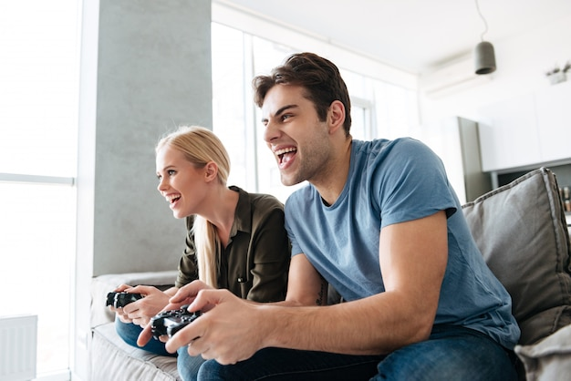 Young gambled lovers playing video games at home