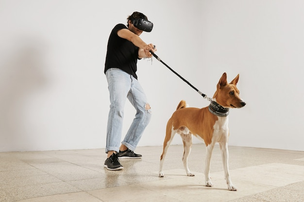 A young gamer in vr headset and black unlabeled t-shirt pulling a leash on brown and white basenji dog on white wall.