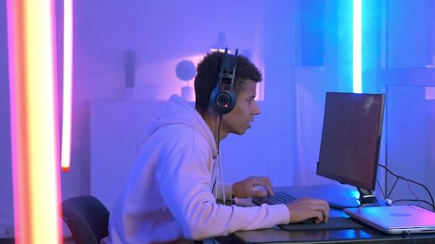 Молодой игрок в наушниках играет в онлайн-шутер