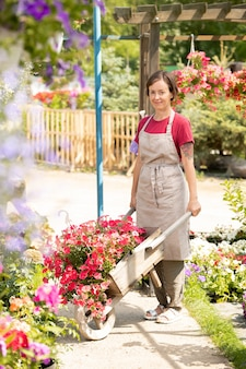温室での作業中に花壇の間の通路にカート立って若い園芸用品センターワーカー